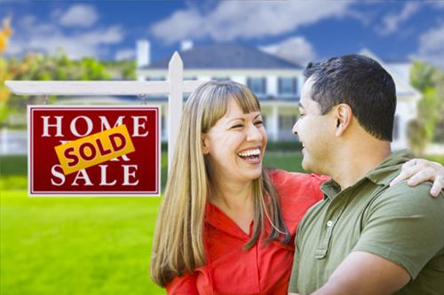 Happy Couple in Front of Sold Home